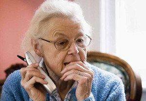 Worried and pensive senior woman talking on cordless phone. Image shot 2006. Exact date unknown.